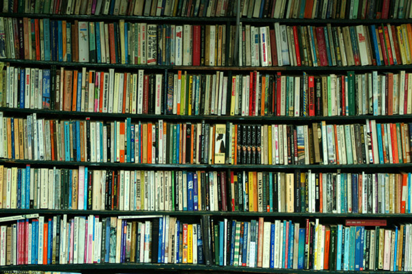 Crowded shelves of books in a bookstore.